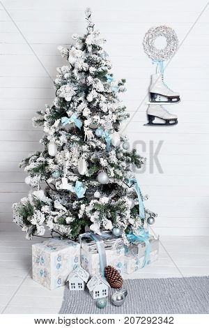 Decorated christmas tree on white background with skates and wreath hanging on the wall. New year decoration, winter holidays