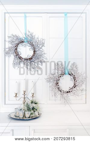 Beautiful Christmas interior. New year decoration. Candles in a metal candlestick and Christmas wreaths