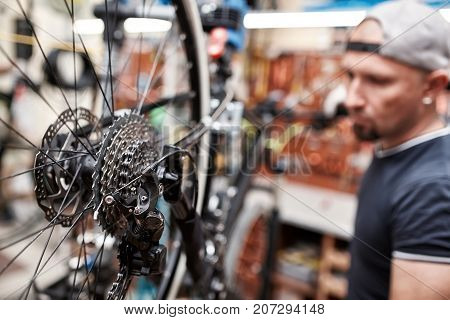 Bicycle mechanic in a workshop in the repair process. Man repair his bike. Mechanic at his workplace