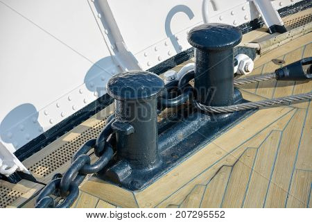 Two Black Bollards On A Wooden Deck On A Ship