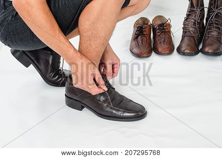 Fashionable Men's Classic Leather Shoes , man ties up his shoelaces on white background with copy space