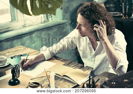 Writer at work. Handsome young writer sitting at the table and writing something in his sketchpad at home