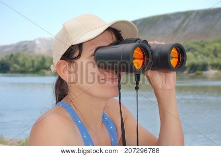 Near the river there is a woman and looks through binoculars. She watches her children and sees beautiful mountains. Holds binoculars with one hand