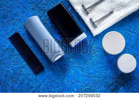 Men's cosmetics for hair care and shaving. Shampoo, gel, razor, wax on blue background top view.