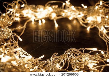 Christmas Frame with glowing lights garland on a old antique wooden parquet floor sparkling garland. Christmas background with festive decoration and copy space