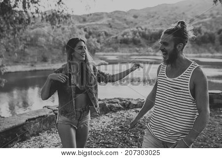 Natural couple enjoying in nature with mountain in the background. Black and white.