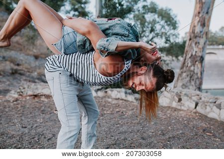 Man and woman in jeans playing together in nature.