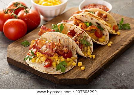Breakfast tacos with scrambled eggs, corn, tomatoes and bacon