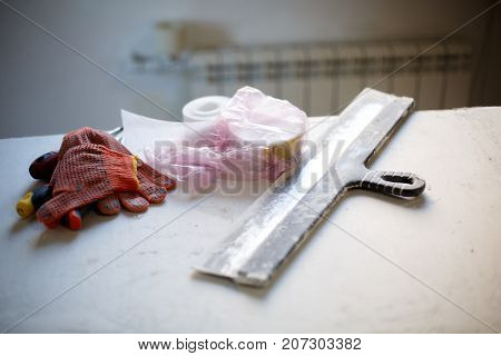 Kind of materials for building. Gloves, spatula, bucket with putty, concrete and other materials. Close-up of objects.