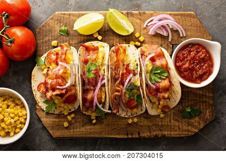 Breakfast tacos with scrambled eggs, corn, tomatoes and bacon overhead shot
