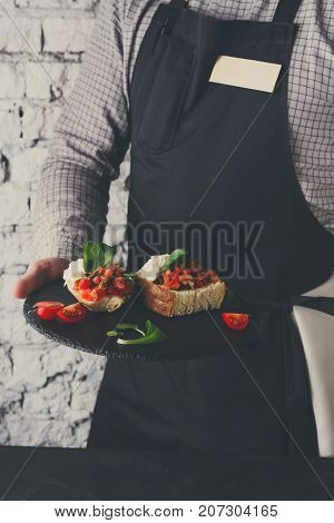 Waiter offering exquisite restaurant dish. Quinoa salad with avocado, cucumber, halloumi cheese and tsadziki sauce on gray plate in unrecognizable male hands. Copy space on apron
