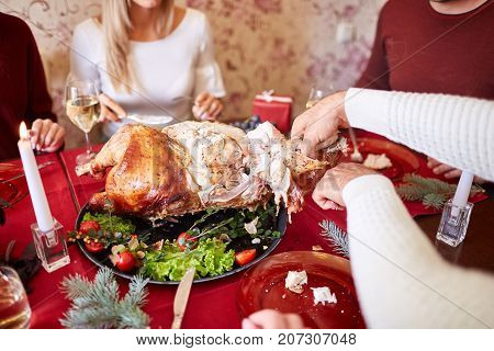 Close-up of a man slicing a hot, roasted turkey with salads and garnish on a celebrating family background. Thanksgiving or Christmas turkey and candles. Thanksgiving Day.