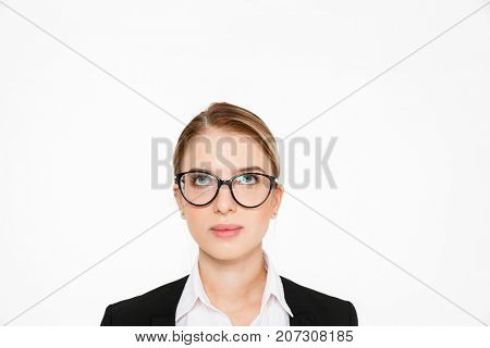 Close up image of carefree blonde business woman in eyeglasses looking up over white background