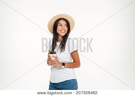 Portrait of a happy brunette woman in hat holding take away coffee cup while standing and looking away at copy space isolated over white background