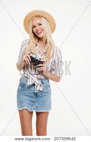 Portrait of an attractive young woman in hat standing and holding camera isolated over white background