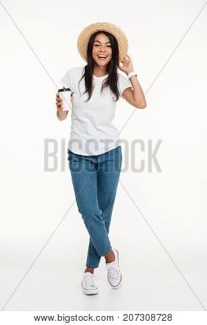 Full length portrait of a happy attractive woman in hat holding take away coffee cup while standing isolated over white background