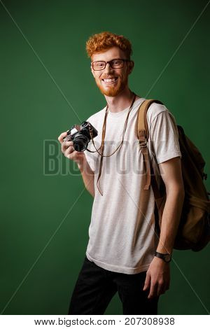 Portrait of smiling readhead bearded hipster with retro camera and backpack, standing over green background