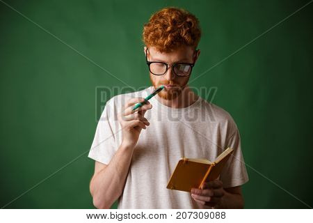 Smart readhead bearded student in glasses reading the notes with pen in his mouth, over green background