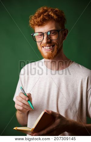 Cheerful readhead bearded student in white tshirt, holding notebook with pen, looking at camera, over green background