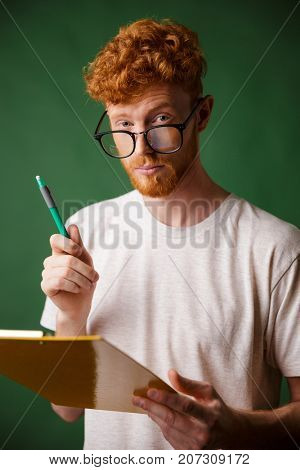Smart readhead bearded man in white tshirt holding folder and pen, looking at camera, over green background