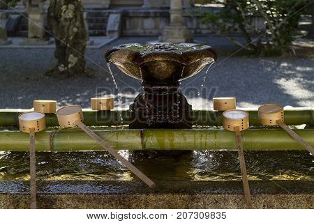 Kyoto, Japan - May 18, 2017: Row of ladles at a lotus shaped purificaton basin near the chion-in shrine