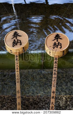Kyoto, Japan - May 18, 2017: Row of ladles at a purificaton basin near the chion in temple