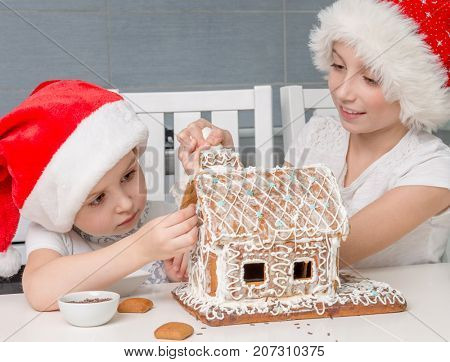 two little sisters in santa hat making biscuit house
