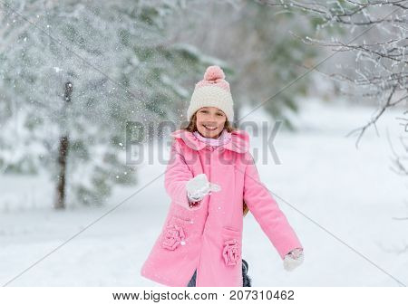 Little girl throws snow up in the air