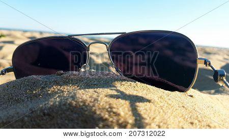 pair of sunglasses on the sand, beach, sea