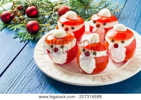 Idea for Christmas party: funny Santa Claus from tomatoes. Tomatoes stuffed with cheese and garlic on plate. Original snack with Christmas and New Year. Blue wood background with Christmas decoration