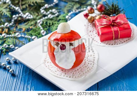 Idea for Christmas party: funny Santa Claus from tomato stuffed with cheese garlic and gift box on plate. Original snack with Christmas and New Year. Blue wood background with Christmas decoration