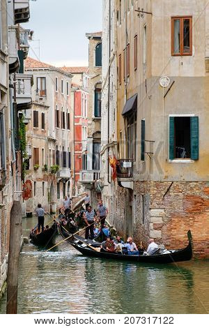 VENICE,ITALY - JULY 26,2017 : Gondolas on a narrow canal surrounded by old buildings in Venice