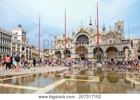 VENICE,ITALY - JULY 26,2017 : St Mark's Square during a flood in Venice with a view of the Basilica and reflections on the water