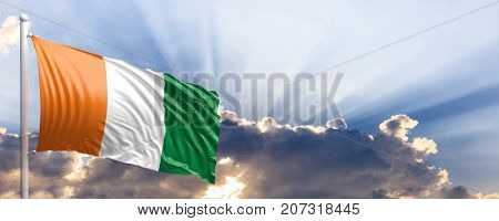 Ivory Coast waving flag on blue sky. 3d illustration