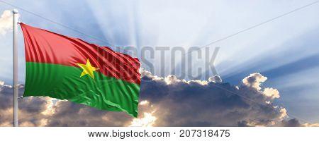 Burkina Faso waving flag on blue sky. 3d illustration