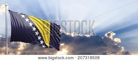 Bosnia and Herzegovina waving flag on blue sky. 3d illustration