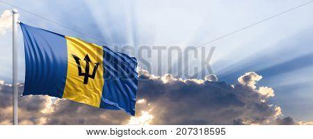 Barbados waving flag on blue sky. 3d illustration