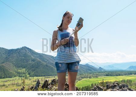 Woman taking selfie on mobile phone with stick. Vacation in the mountain