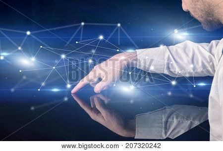 Male hands touching interactive table with blue connectivity graphic in the background