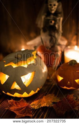 Halloween decorations. Spooky jack-o-lanterns burning in darkness, autumn leaves and scull
