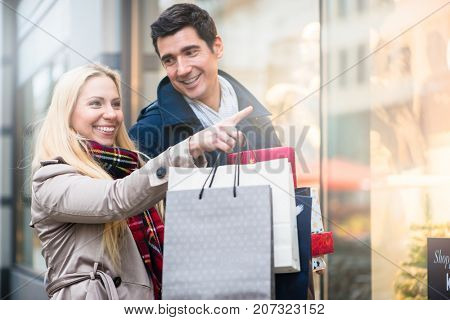 Couple, man and woman, at shop window doing Christmas shopping