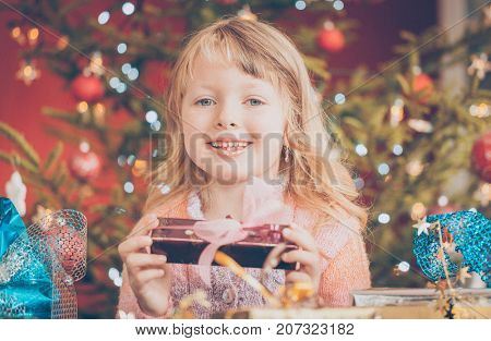 Happy at Christmas is unwrapping presents under the tree lit with candles