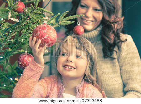 Young girl helping her mother decorating the Christmas tree, holding some Christmas baubles in her hand