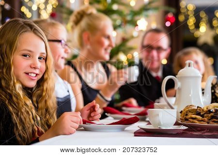 Parents and children celebrating Christmas with drinking coffee eating and X-mas cookies