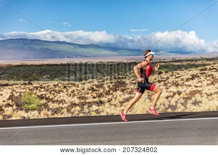 Triathlete man runner running uphill, on road at triathlon suit training for ironman. Male athlete exercising on Big Island Hawaii, USA. Fitness in summer landscape.