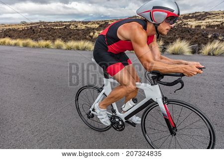 Triathlon biking cyclist man triathlete riding racing bike during ironman competition. Road cycling athlete in tri suit and helmet.