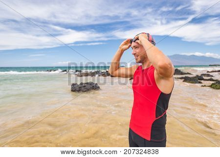 Man triathlete swimmer putting on swim goggles - Triathlon sport athlete going swimming getting ready an ocean swim. Fit man in professional triathlon suit training for ironman.