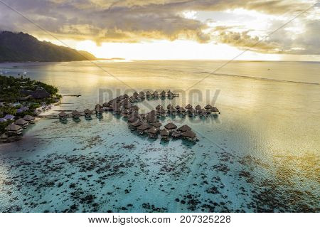 Luxury travel vacation aerial of overwater bungalows resort in coral reef lagoon ocean by beach. View from above at sunset of paradise getaway Moorea, French Polynesia, Tahiti, South Pacific Ocean.