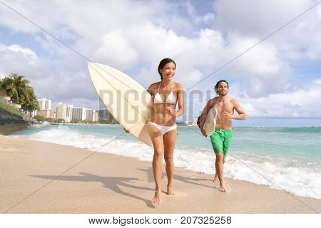 Hawaii Waikiki beach surfers having fun going surfing. Multiracial couple running out of water with surfboards after surf lesson.