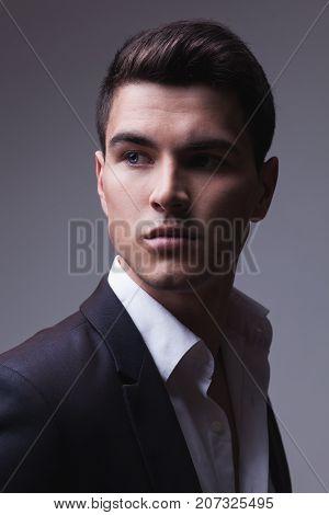 Closeup studio portrait of of a handsome man wearing suit. Light grey gradient studio background.
